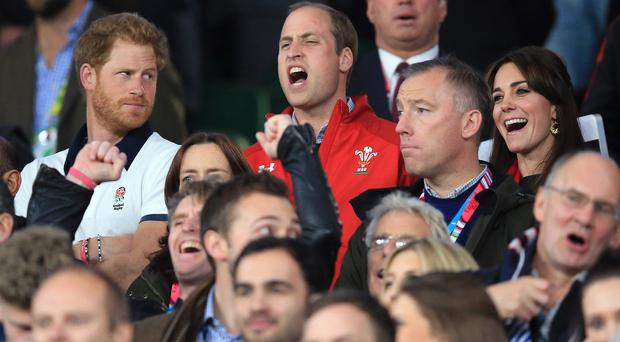 The look from Prince Harry (left) says it all as William and Kate cheer Wales