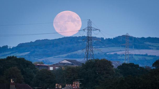 The moon rises over electricity pylons near Bath ahead of a lunar eclipse