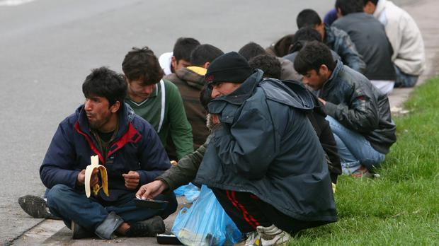 Men sit and eat food handouts at a migrant camp in the French port town of Calais