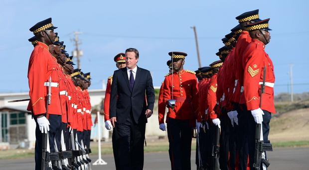 Prime Minister David Cameron inspects a Guard of Honour as he arrives at the airport in Kingston, Jamaica as part of a two day visit to the Caribbean.
