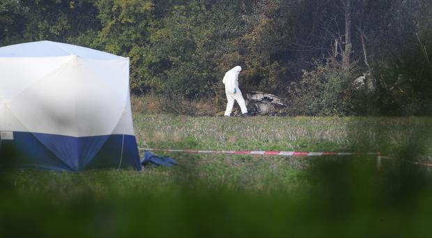 Forensics officers at the scene of a light aircraft crash where two people died in a field off Gravel Lane in Chigwell