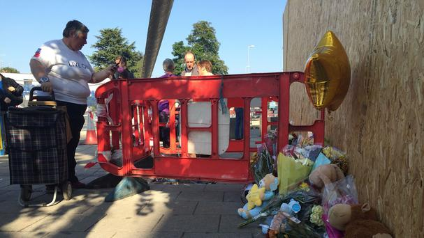 Floral tributes left at the scene outside the Sainsbury's store in Trinity Street, Coventry