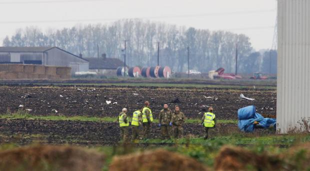 Police at a field in Redmere, Cambridgeshire, strewn with wreckage from the US fighter jet which crashed near RAF Lakenheath