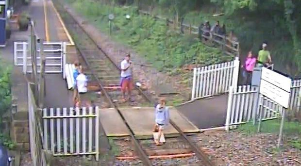 Vdeo grab of a man taking a picture of a child on the track at Matlock Bath station in Derbyshire (Network Rail/PA)