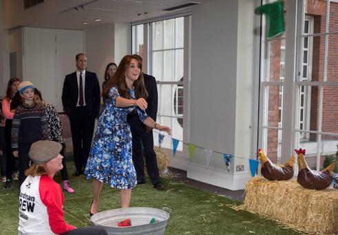 The Duchess of Cambridge and Prince Harry try their hand at welly-wanging during a meeting of the Charities Forum yesterday