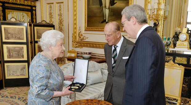 The Queen, the Duke of Edinburgh and Australian High Commissioner, Alexander Downer, as she presented Philip with the Insignia of a Knight of the Order of Australia