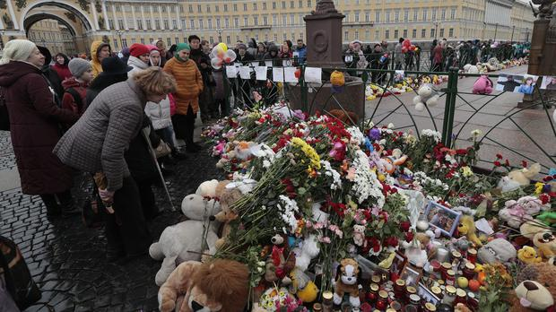 People lay flowers in memory of the plane crash victims at Dvortsovaya (Palace) Square in St Petersburg (AP)