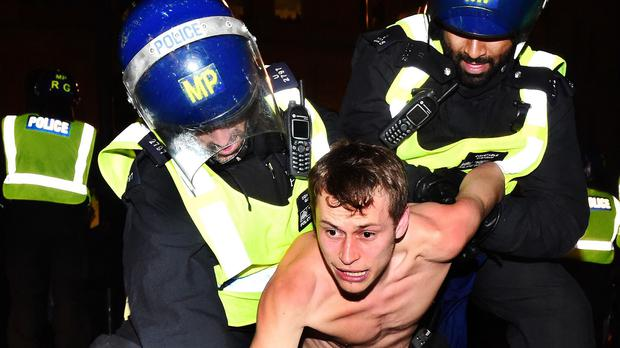 A man is detained by police in Trafalgar Square, London during the Million Mask March bonfire night protest organised by activist group Anonymous