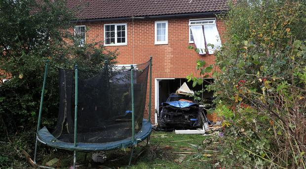 A car crashed through a garden of a home in Ashford in Kent and embedded itself backwards into a house narrowly missing the occupants of the home