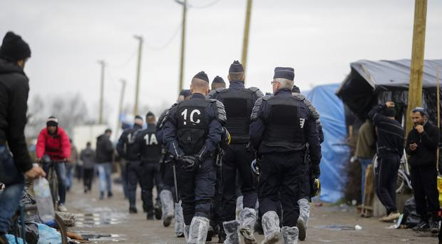 Police patrol through the migrant camp near Calais with their boots covered in plastic bags to protect against the mud (AP)