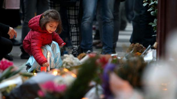 A young girl leaves a lit candle outside Le Carillon bar, Paris, one of the venues for the attacks