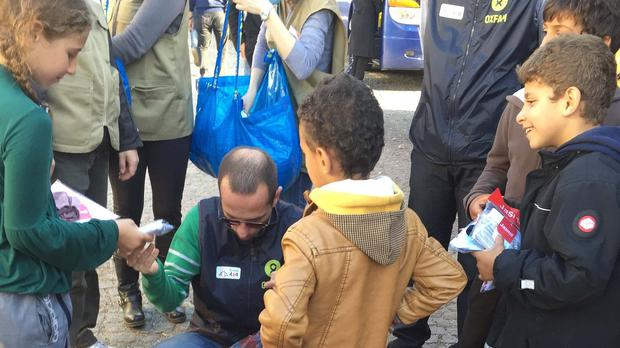 Dobrivoje Stancic, Oxfam's humanitarian affairs co-ordinator in Serbia, hands out socks and underwear to refugee children