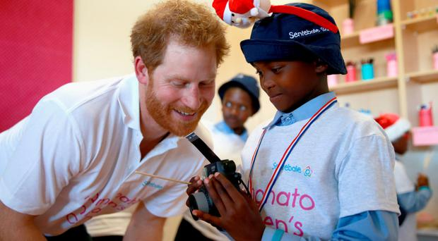 Prince Harry helps a boy use a camera at the Mamohato Children's Centre in Lesotho, yesterday