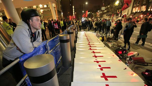 Protesters gather around mock coffins during a 'die in' rally outside Transport for London's headquarters in London