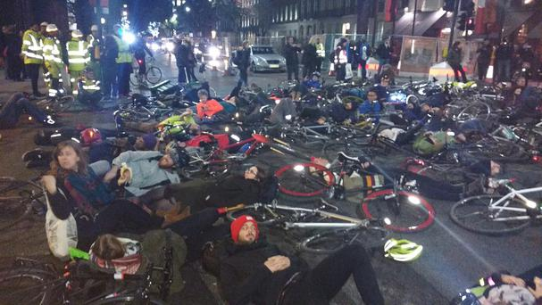 Cyclists lie in the road during a