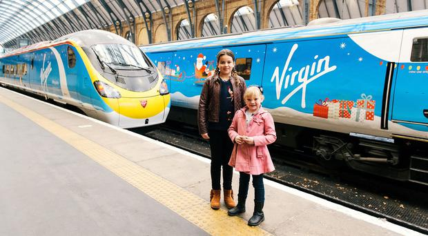 Madeline Deakin, 11, left, and Amber Maxwell, nine, were behind the designs on the Virgin Christmas trains unveiled at Kings Cross Station (Virgin Trains/PA)
