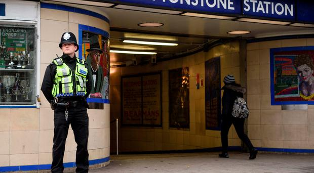 A police officer stands guard outside Leytonstone stationwith