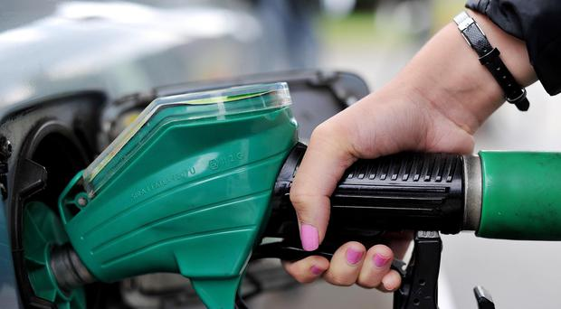 A person using a petrol pump, as supermarkets cut the price of fuel