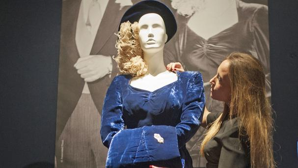 A Christie's staff member adjusts Margaret Thatcher's wedding outfit