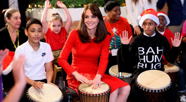The Duchess of Cambridge takes part in a drumming session at a Christmas party yesterday