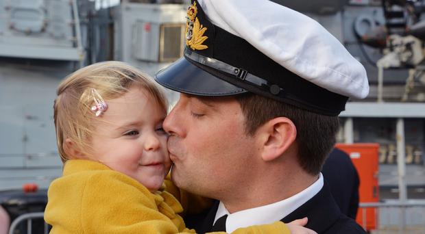 Lieutenant Commander Nick London, 35, from Alverstoke, Hampshire, gives his daughter Rosalie a kiss as he returns aboard HMS Lancaster to Portsmouth Naval Base