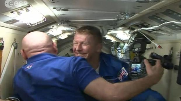 An image taken from footage issued by the European Space Agency shows Major Tim Peake emerging from the Soyuz space capsule hatch at the the International Space Station
