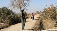 An Afghan soldier stops a motorbike at a checkpoint in the Nad Ali district of Helmand province (AP)