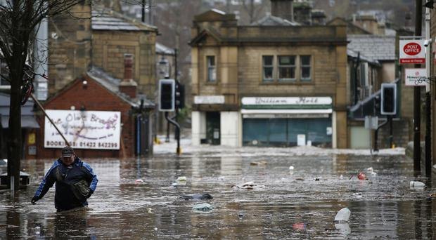 A man wades through flood waters at Hebden Bridge, where flood sirens were sounded after torrential downpours
