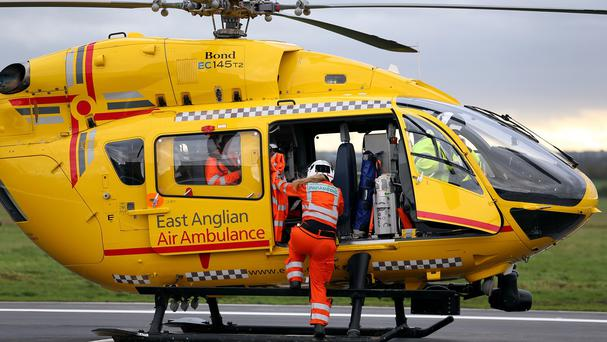 East Anglian Air Ambulance crew member Jemma Varela makes her way to the helicopter after the crew received a call to attend a road traffic accident in Fakenham, Norfolk