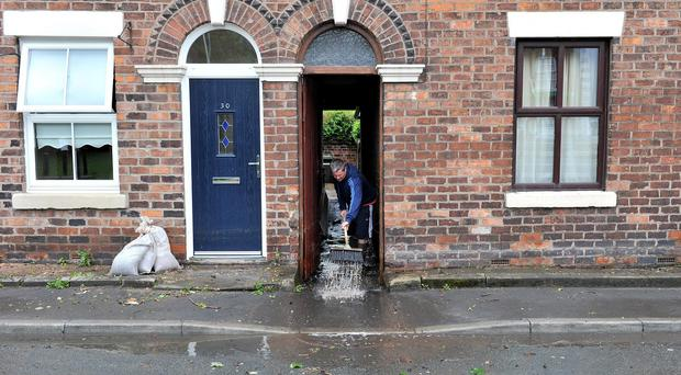 A villager clears water from his home in Croston, Lancashire, after flooding in 2012