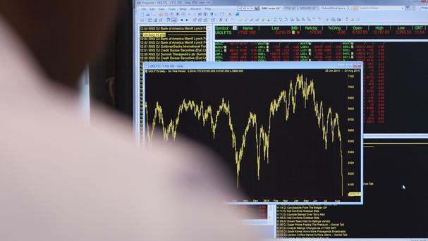 An office worker views a graph showing movement in the FTSE 100 Index