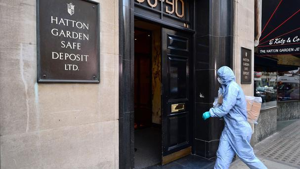 A police forensics officer enters the Hatton Garden Safe Deposit company