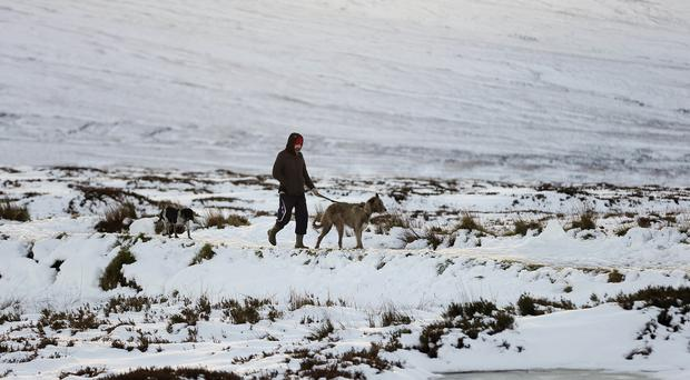 A person walks through snow covered fields in Killakee in Dublin as Britain is bracing itself for an icy blast over the coming week.