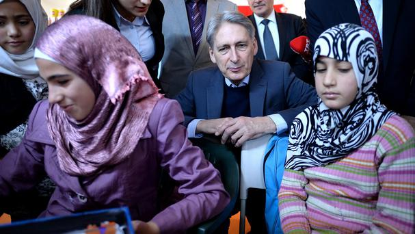 Foreign Secretary Philip Hammond, centre, meets children taking lessons during a visit to the Saricam refugee camp near Adana in Turkey