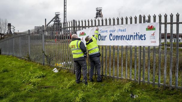 Security staff take down a Unite union banner on the fence outside the Tata steel plant in Port Talbot
