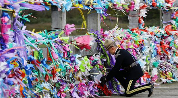 A member of the Legion of Frontiersmen lays a wreath on the Old Shoreham Tollbridge as a memorial service took place for the victims of the air crash