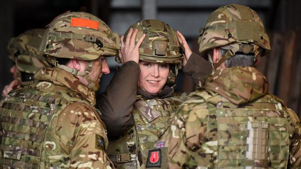 Armed Forces Minister Penny Mordaunt adjusts her helmet before watching a live firing exercise