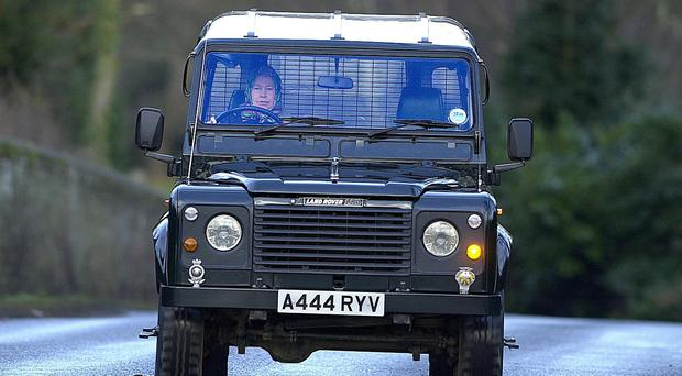 The Queen driving herself in a Land Rover Defender