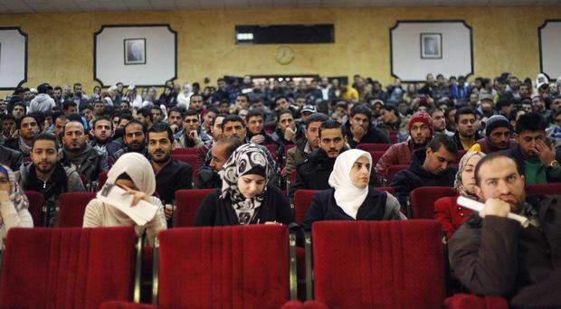 Syrian refugee students attend an open house at Zarqa University in Zarqa, Jordan, as King Abdullah warned the 'dam is going to burst' in his country (AP)