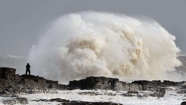 Waves crash over rocks at Porthcawl in Wales as winds of nearly 100mph battered Britain after Storm Imogen slammed into the south coast bringing fierce gusts and torrential downpours.