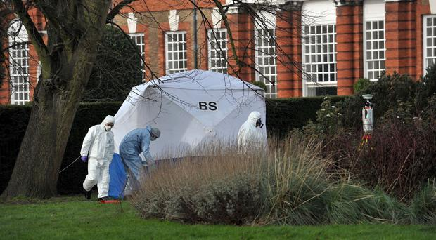 Forensic officers search an area where a man was found on fire near Kensington Palace