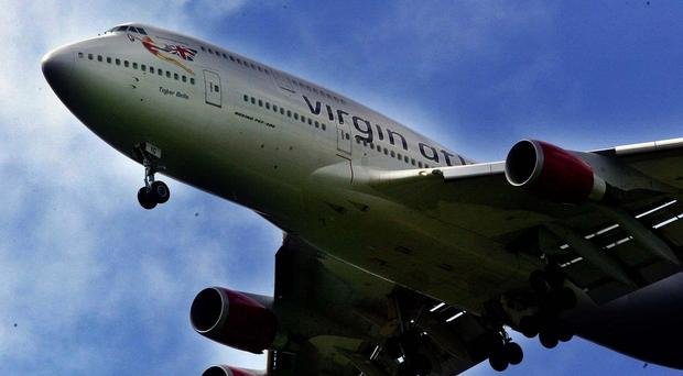 A Virgin Atlantic co-pilot was taken ill when a laser was shone into the cockpit after take-off from Heathrow