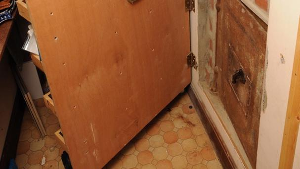 A hidden door to a safe in the home of James Arnold where the biggest hoard of illegal weapons ever found in the UK was found (Suffolk Police/PA)
