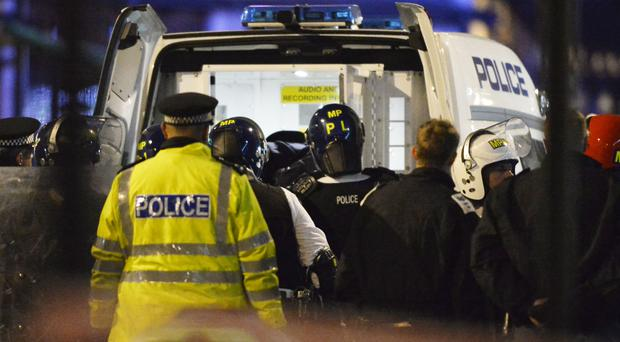 A man is taken into a police van outside the Bella Italia restaurant in Leicester Square