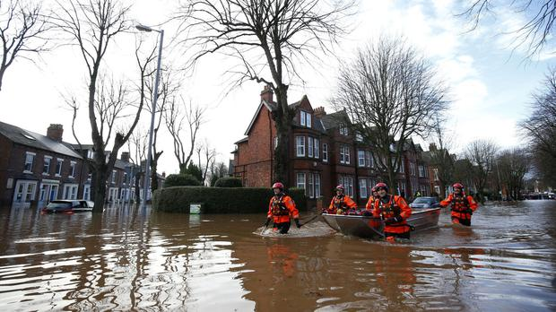 Emergency workers wade through floodwater in Carlisle after heavy rain from Storm Desmond