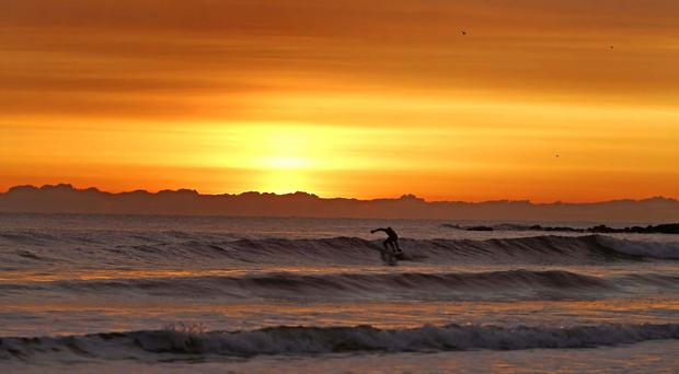 A surfer braves the cold as the sun rises on Tynemouth Beach, North Tyneside, on the last day of meteorological winter