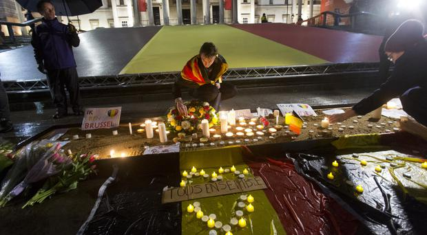 People leave flowers, candles and other tributes during a vigil in Trafalgar Square, central London, to mark the terror attacks in Brussels