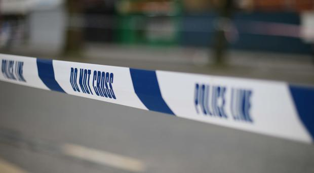 Police have cordoned off an area around a shop where the owner was attacked