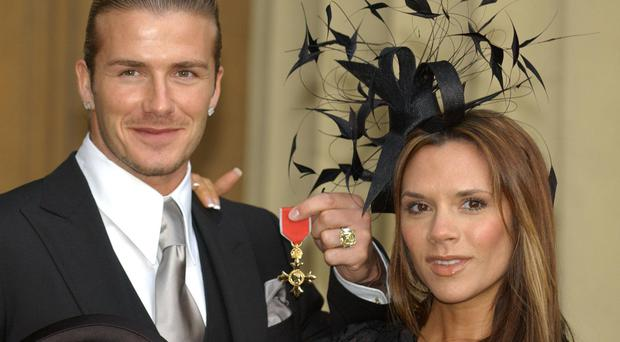 David Beckham with his wife Victoria after receiving his OBE