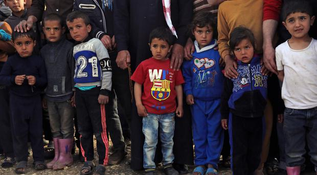 Syrian refugees wait for UN Secretary-General Ban Ki-moon to arrive for a visit, at a refugee camp in Lebanon (AP)